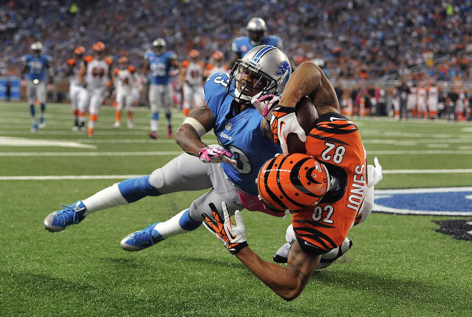 Cincinnati Bengals' Marvin Jones (82) catches a 12-yard touchdown as Detroit Lions cornerback Chris Houston (23) defends in the second quarter of an NFL football game on Sunday, Oct. 20, 2013, in Detroit. Photo: Jose Juarez, ASSOCIATED PRESS / AP2013