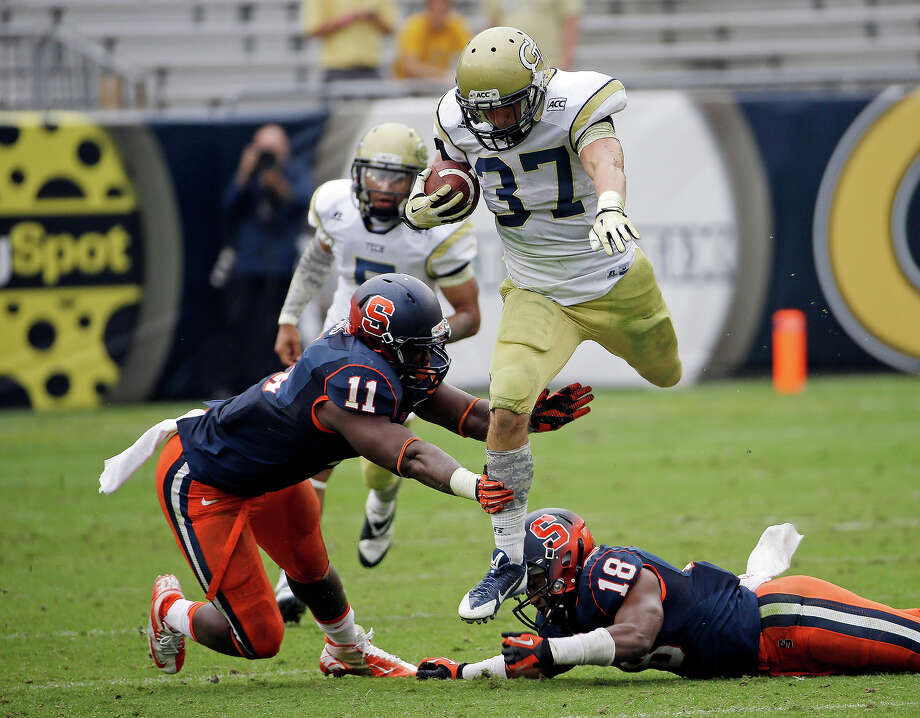 Georgia Tech running back Zach Laskey (37) gets away from Syracuse linebacker Marquis Spruill (11) and defensive back Darius Kelly (18) in the second half of an NCAA college football game Saturday, Oct. 19, 2013, in Atlanta. Tech won 56-0. Photo: John Bazemore, AP / AP