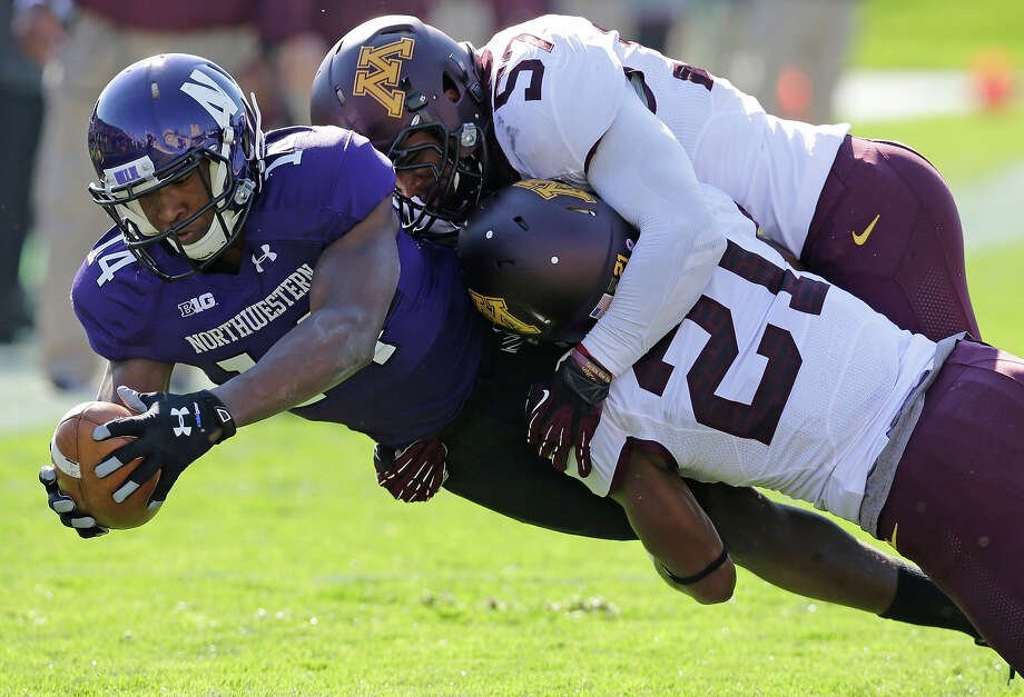 Minnesota defensive back Brock Vereen (21) and linebacker Aaron Hill (57) tackle Northwestern wide receiver Christian Jones (14) during the first half of an NCAA college football game in Evanston, Ill., Saturday, Oct. 19, 2013. Photo: Nam Y. Huh, AP / AP