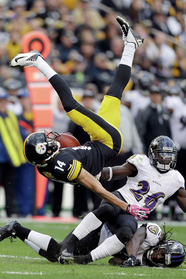 Pittsburgh Steelers wide receiver Derek Moye (14) flips over after making a catch over Baltimore Ravens free safety Matt Elam (26) and cornerback Lardarius Webb in the second quarter of an NFL football game in Pittsburgh on Sunday, Oct 20, 2013. Photo: Gene J. Puskar, ASSOCIATED PRESS / AP2013