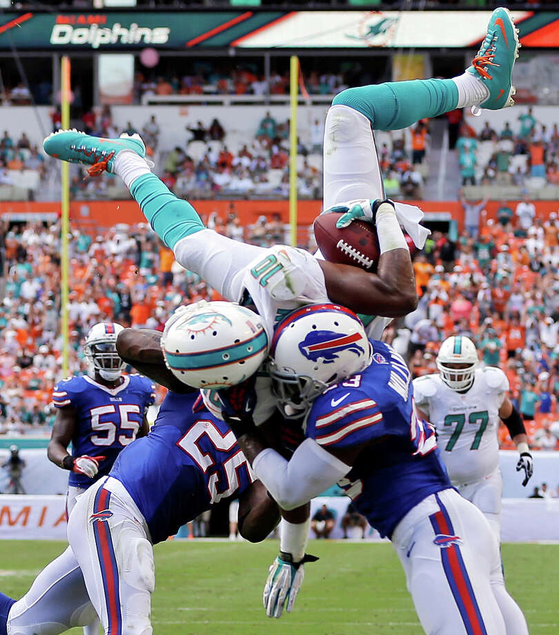 Miami Dolphins wide receiver Brandon Gibson (10) jumps over Buffalo Bills free safety Aaron Williams (23) and strong safety Da'Norris Searcy (25) for a touchdown during the first half of an NFL football game, Sunday, Oct. 20, 2013, in Miami Gardens, Fla. Photo: Lynne Sladky, ASSOCIATED PRESS / AP2013