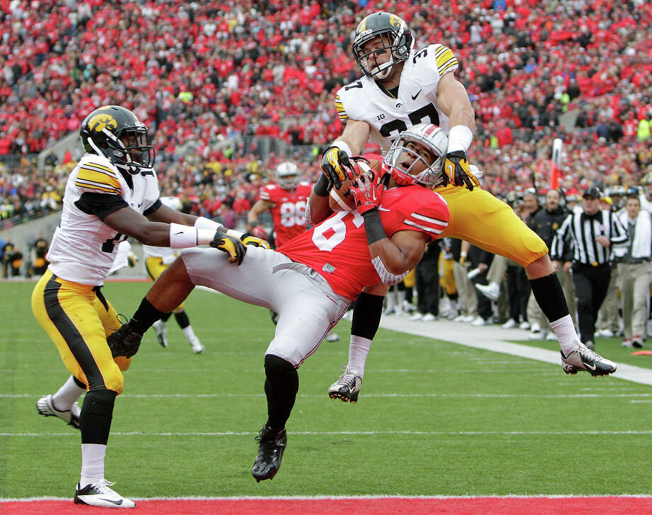 Iowa defensive backs Desmond King, left, and John Lowdermilk, right, break up a pass intended for Ohio State wide receiver Evan Spencer, center, during the second quarter of an NCAA college football game Saturday, Oct. 19, 2013, in Columbus, Ohio. Photo: Jay LaPrete, ASSOCIATED PRESS / AP2013
