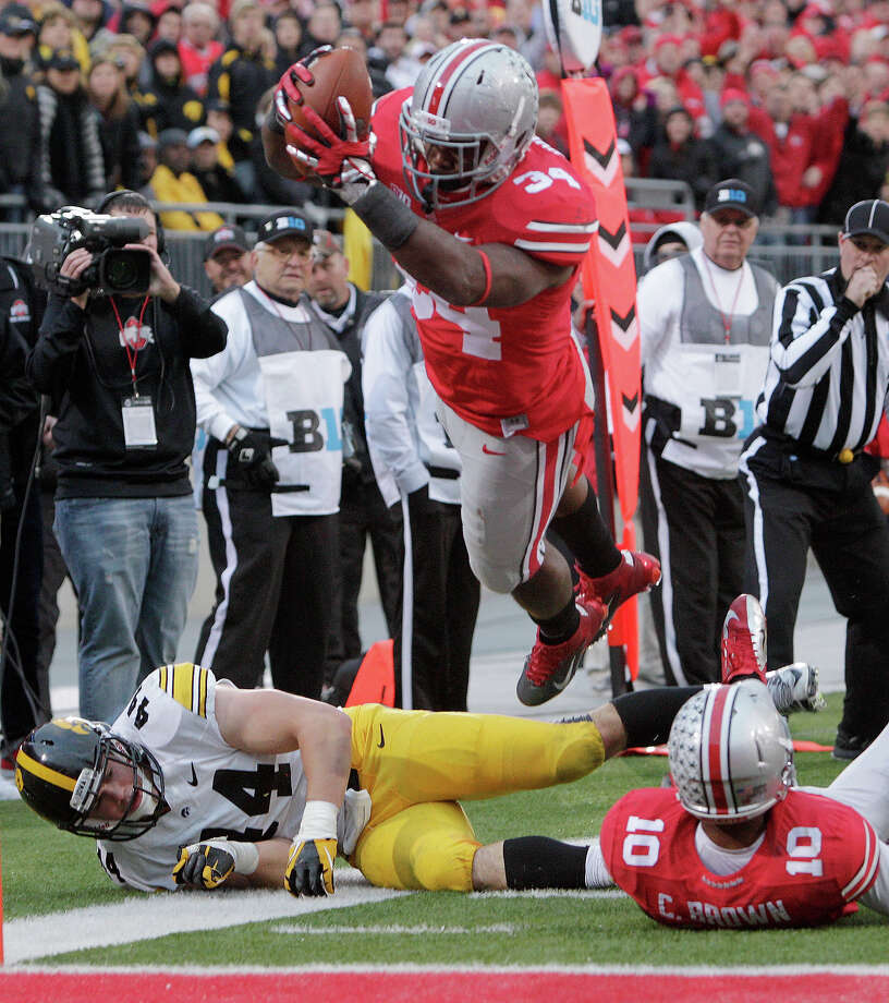 Ohio State running back Carlos Hyde, top, dives over the goal line to score a touchdown past teammate Corey Brown, right, and Iowa linebacker James Morris during the fourth quarter of an NCAA college football game Saturday, Oct. 19, 2013, in Columbus, Ohio. Ohio State beat Iowa 34-24. Photo: Jay LaPrete, ASSOCIATED PRESS / AP2013