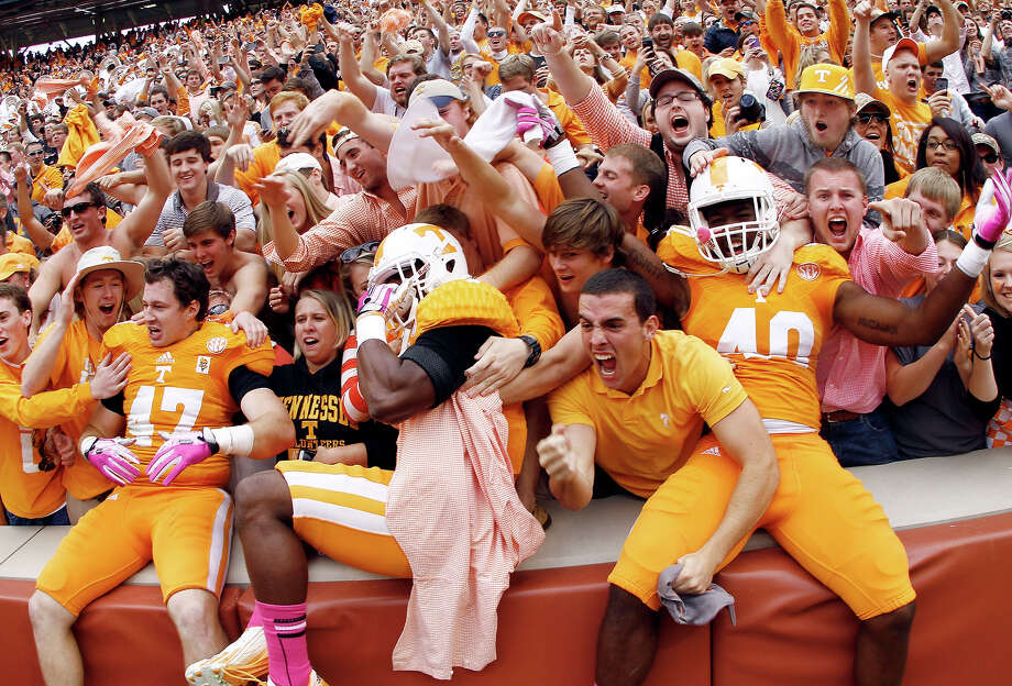 Tennessee linebacker Raiques Crump (40), defensive back Michael F. Williams, center, and linebacker John Propst (47) celebrate with fans after their 23-21 victory over South Carolina in an NCAA college football game on Saturday, Oct. 19, 2013 in Knoxville, Tenn. Photo: Wade Payne, AP / FR23601 AP