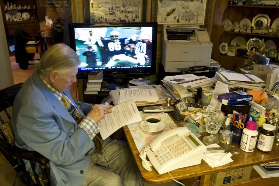 Bud Adams looks over papers while watching football on television at his home in 2009. Photo: Brett Coomer, Houston Chronicle
