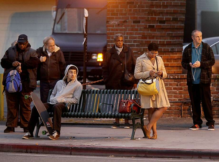 Transbay commuters wait at an AC Transit bus stop in Oakland on Monday, the fourth and final day of the BART strike. Photo: Brant Ward, The Chronicle