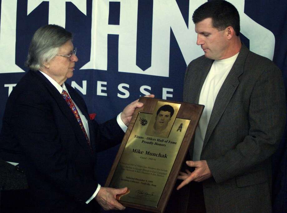 K. S. 'Bud' Adams, left, presents Mike Munchak with a plaque comemorating his induction in to the Titans/Oilers Hall of Fame for his play as guard for the Houston Oilers from 1982-1993 on Thursday, Dec. 9, 1999. Photo: George Walker IV, Associated Press