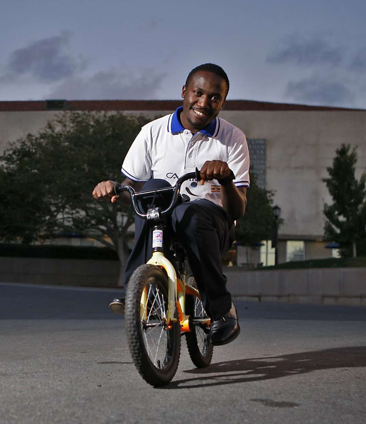 Chris Ategeka sits on a small bicycle for a portrait at U.C. Berkeley, Saturday, Sept. 21, 2013.