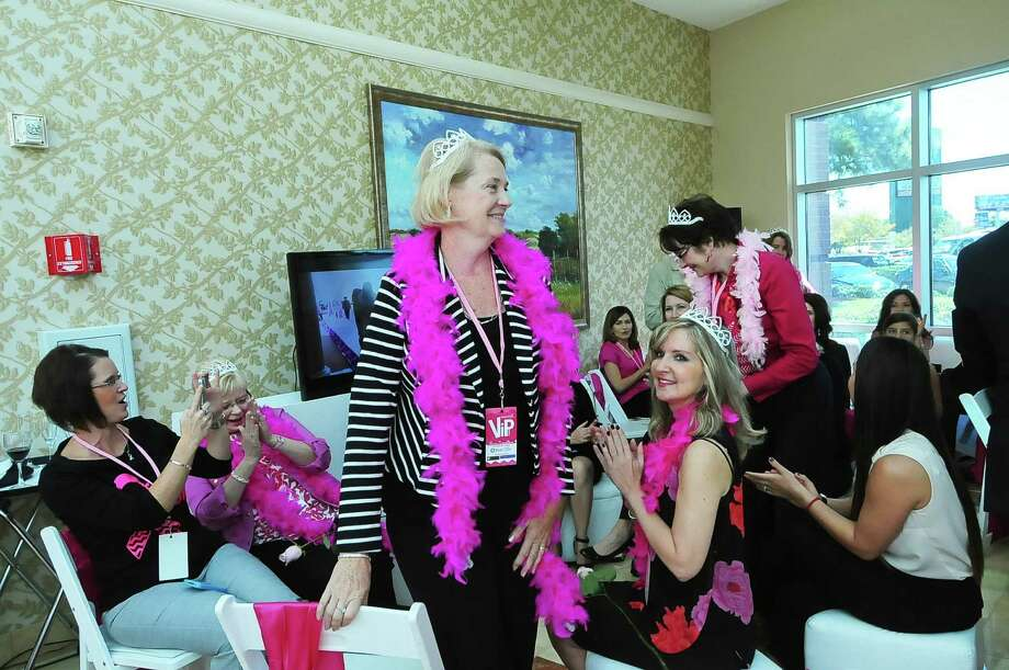 As Shannon Bratton  takes a photo, and Louise Bratton  applauds, Priscilla Avery  stands up to be recognized as a survivor and Sara Lewandowski applauds herself during the North Cypress Medical Center Project Pink 2013 event benefiting the Houston affiliate of Susan G. Komen for the Cure  on Oct. 19. Anyone wearing a tiara is a breast cancer survivor at this event. Photo: © Tony Bullard 2013, Tony Bullard / © Tony Bullard & the Houston Chronicle