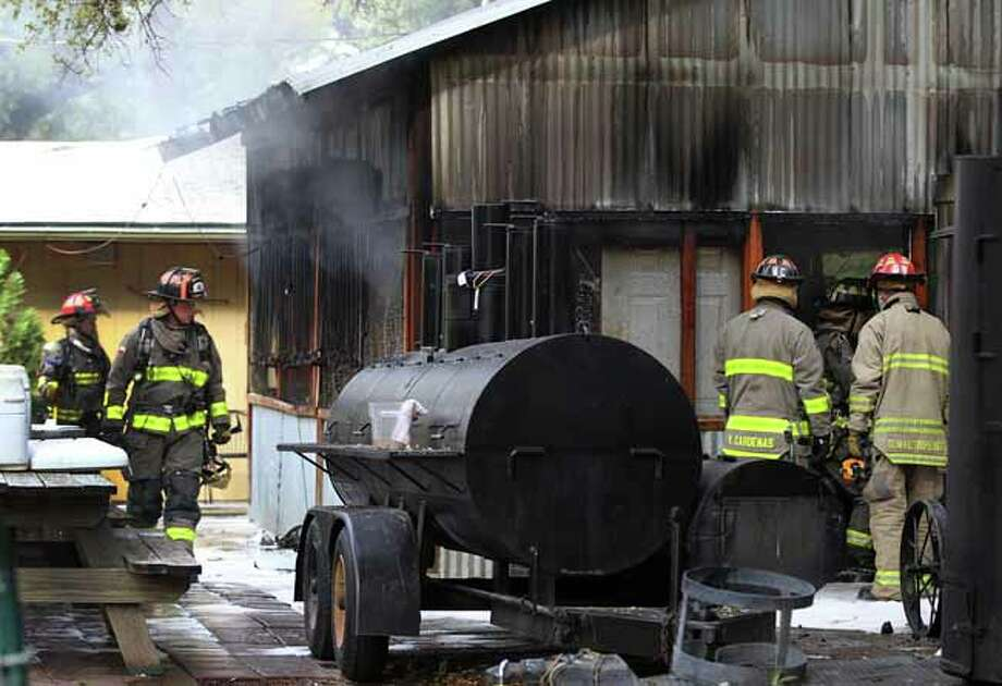San Antonio firefighters work Monday morning October 21, 2013 where a fire broke out at Two Bros. BBQ Mkt. restaurant at 12,656 West Avenue. The fire broke in the detatched smokehouse behind the restaurant and was quickly extinguished. The cause of the fire is being investigated. Photo: JOHN DAVENPORT, SAN ANTONIO EXPRESS-NEWS / ©San Antonio Express-News/Photo may be sold to the public