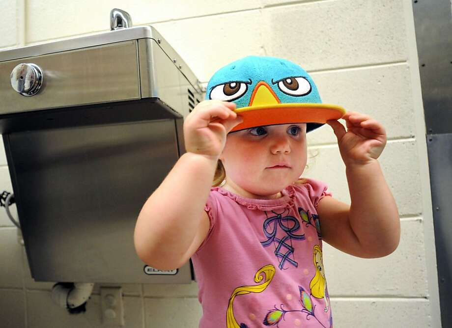 Angry forehead: Two-year-old Phoenix Schrum, a resident of the Daniel Pitino homeless shelter in Owensboro, Ky., tries on a 