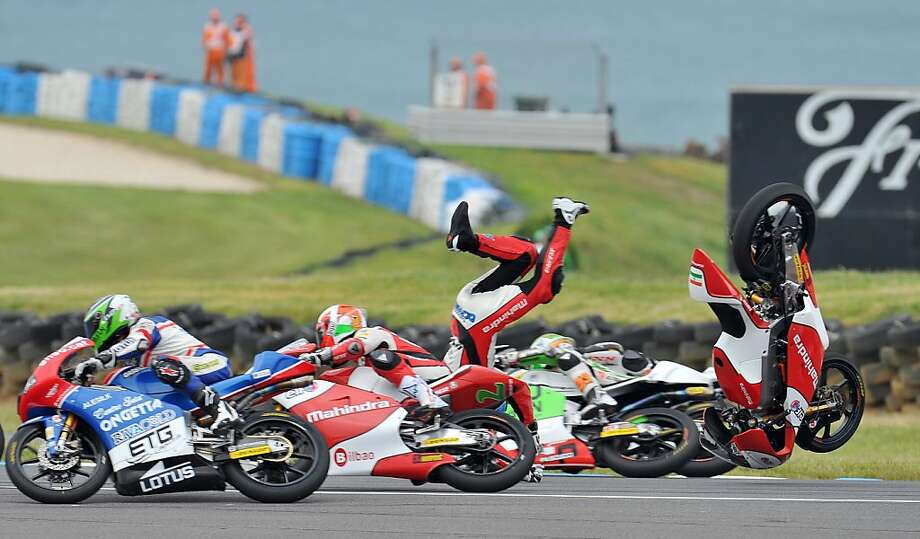 Head over wheels:Mahindra Racing rider Miguel Oliveira of Portugal flies off his bike during the Moto3   race at the Australian Grand Prix, Phillip Island. He brushed himself off and got back in the saddle. Photo: Paul Crock, AFP/Getty Images