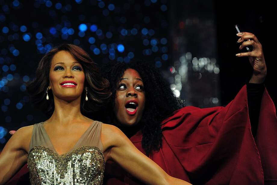 Wax Whitney: A member of London Gospel Factory Choir takes a photo of herself with the waxwork of late singer Whitney Houston at Madame Tussauds in London. Photo: Carl Court, AFP/Getty Images