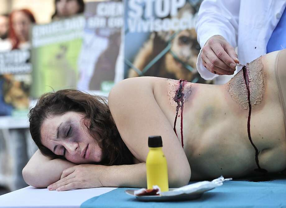 This won't hurt a bit: A fake researcher pretends to cut into his subject during an AnimaNaturalis demonstration against   vivisection and experiments on animals in Barcelona's Sant Jaume Square. Photo: Josep Lago, AFP/Getty Images