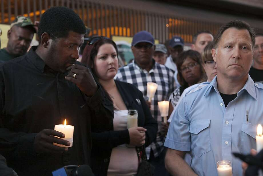 Union members Nucion Avent and Richard Lazzaro honor two workers killed in a train accident. Photo: Eric Slomanson, Associated Press
