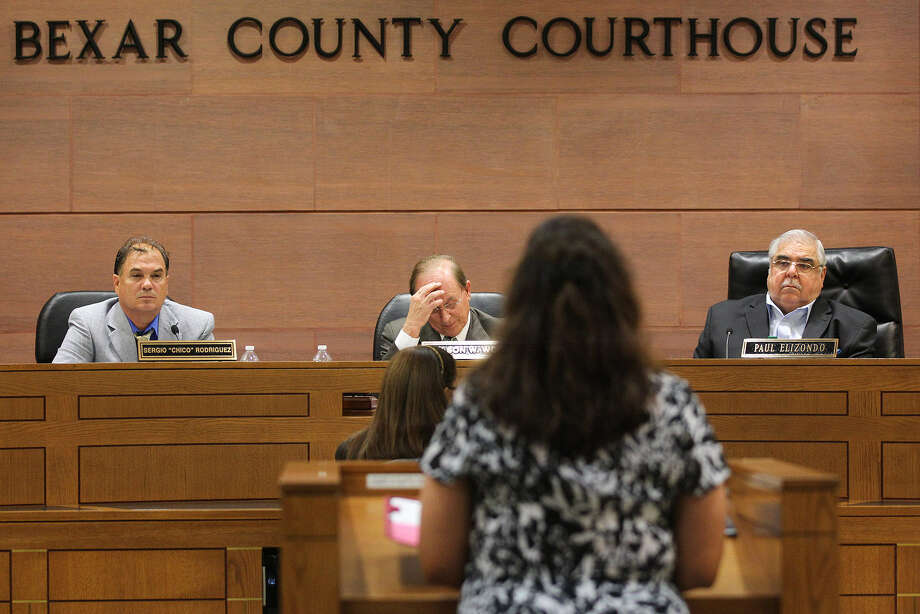 County Commissioners Sergio Rodriguez (left) and Paul Elizondo (right) and County Judge Nelson Wolff listen to a constituent. The officials are rushing toward the unnecessary creation of new justice of the peace courts. Photo: Jerry Lara / San Antonio Express-News