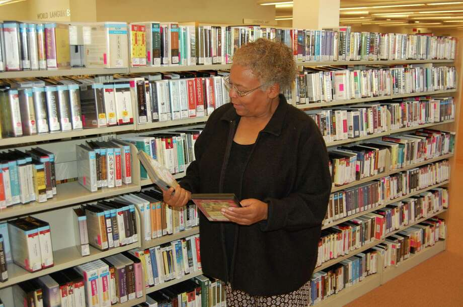 "Audiobooks are a big hit at Greenwich Library, according to Training Librarian Jasmine Posey, who is seen here looking for her next book to listen to. In addition to favorite authors, audiobook fans often have favorite readers, says Posey. ìWe all have likes and dislikes,î Jasmine says. ìSome people prefer to listen to a man or woman only, and then you have your groupies."" Photo: Contributed Photo / Greenwich Citizen"