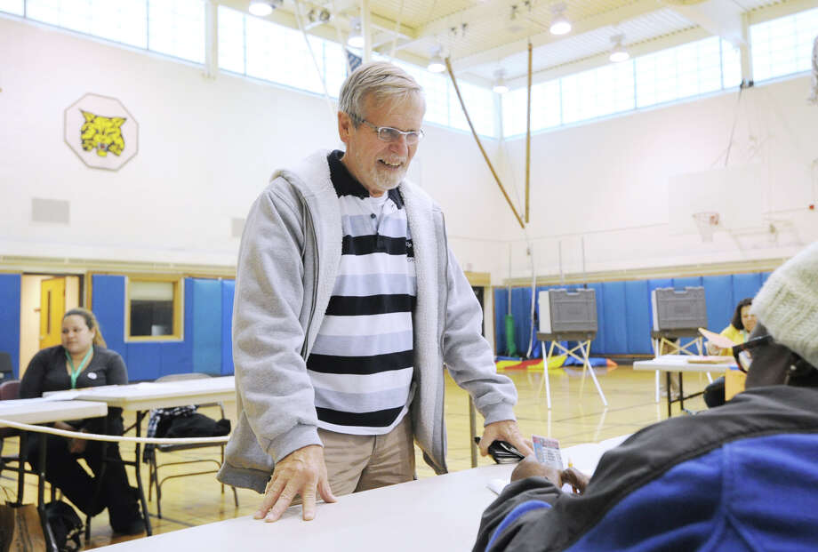 Greenwich High School boys swimming coach, Terry Lowe, left, has his identification checked by poll worker Rosemary Ralph, before Lowe voted at Western Middle School in Byram, Tuesday afternoon, November 6, 2012. Photo: Bob Luckey / Greenwich Time