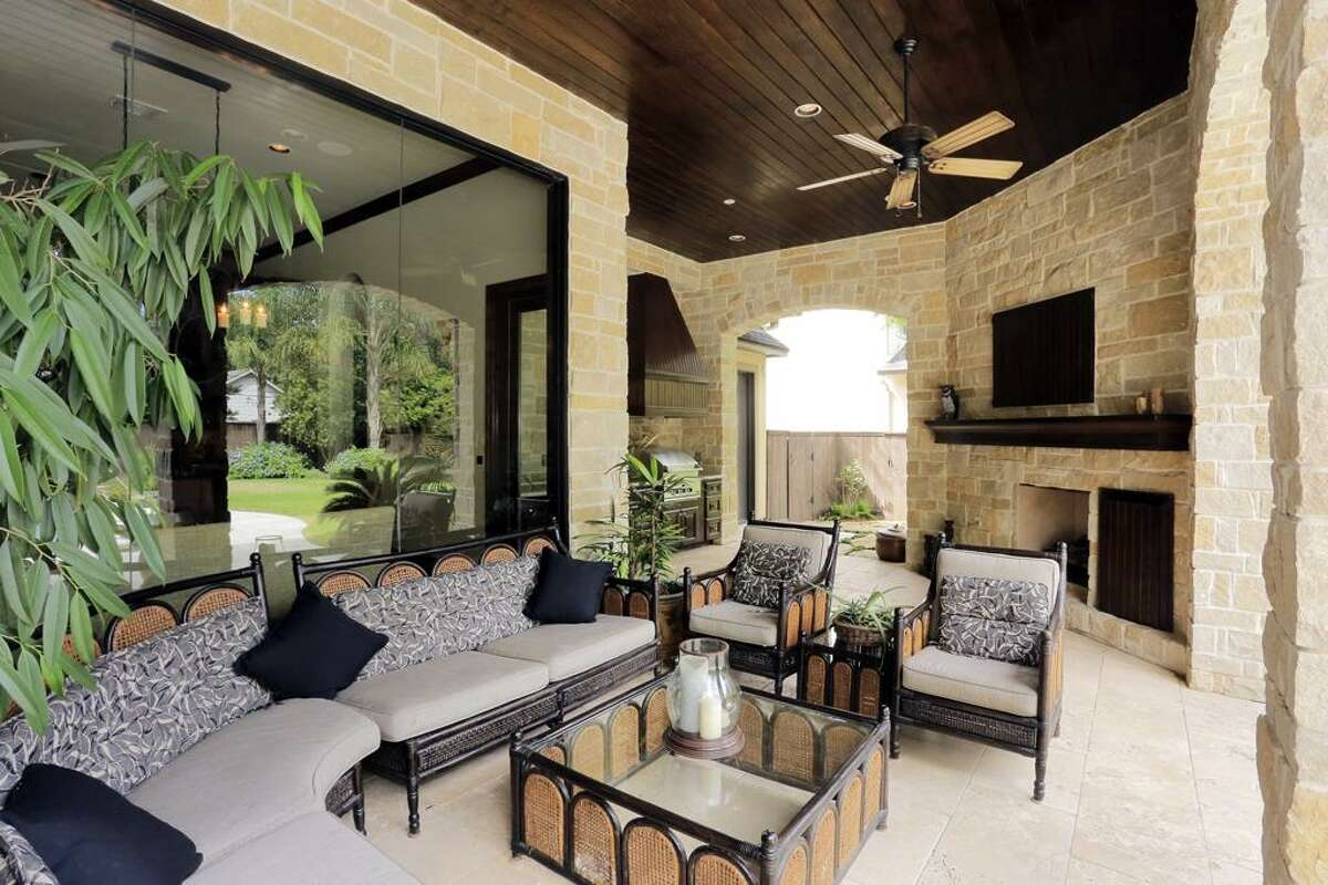The large patio includes a fireplace, outdoor kitchen and television setup.