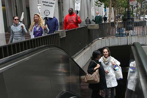 Simoina Vasen (middle left) from San Francisco and Sara Otepka (white coat) from Seattle come up the Muni escalator as members of the Amalgated Transit Union support the Bart strike on Market at Drumm streets in San Francisco, California, on Monday, October 21, 2013.
