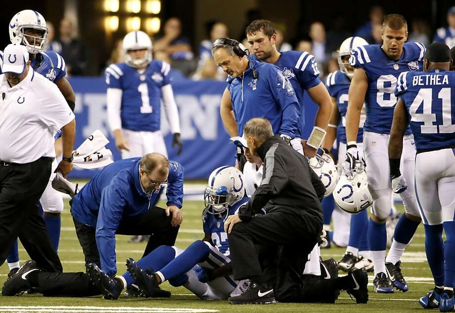 Colts staff members and players gather around as Reggie Wayne receives medical attention during Sunday's game. Photo: Sam Riche, McClatchy-Tribune News Service