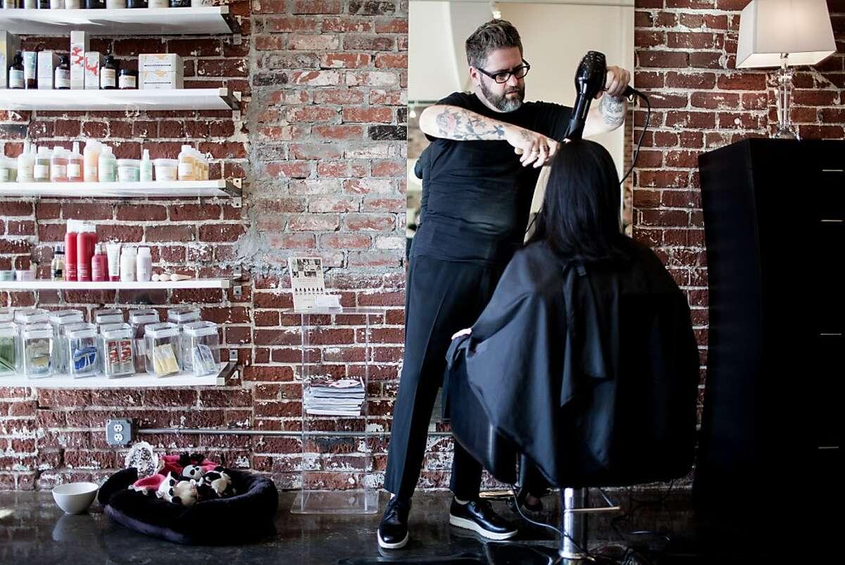 Julia Tanghetti gets a trim from hair stylist Heath Hamilton at the Muse hair salon in Sacramento, California, October 11, 2013.