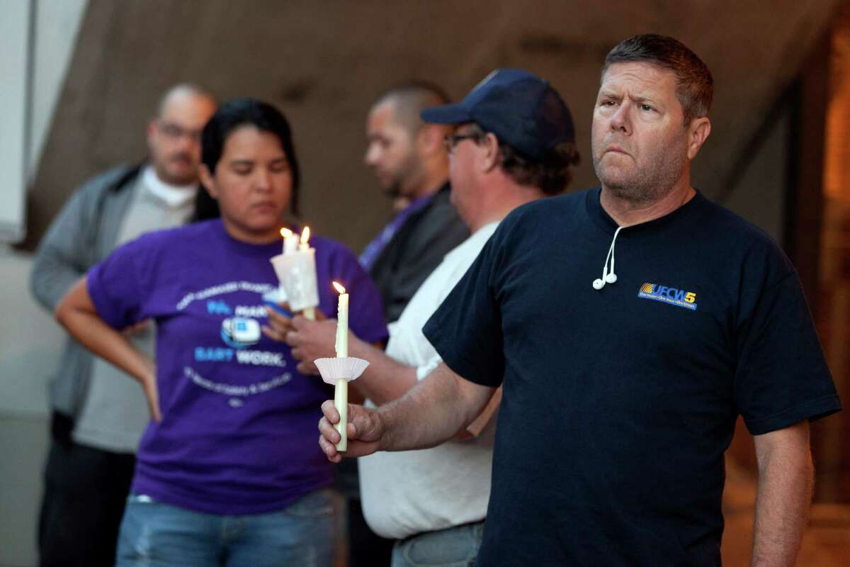 Jack Landes holds a candle to honor the memory of two workers who were killed during a train accident in Walnut Creek, Calif., Sunday, Oct. 20, 2013. Two federal accident investigators arrived in the San Francisco Bay area on Sunday to examine the deaths of two transit workers who on Saturday, were struck by an out-of-service commuter train performing routine maintenance against the backdrop of a labor strike.