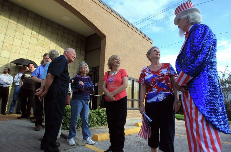 Dressed as Uncle Sam, Kingwood'sJohn Evans speaks with Beverly Mire, of Spring, as they wait for doors to open for the welcome-home event for Senator Ted Cruz on Monday, Oct. 21, 2013, in Houston. Photo: Mayra Beltran, Houston Chronicle / © 2013 Houston Chronicle