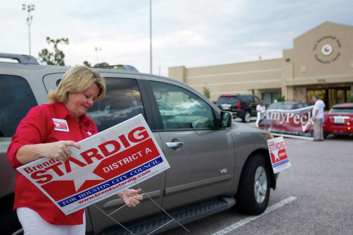 Brenda Stardig, who is running for the Houston City Council District A seat puts out campaign signs outside an early voting site at the Trini Mendenhall Sosa Community Center Monday, Oct. 21, 2013, in Houston.