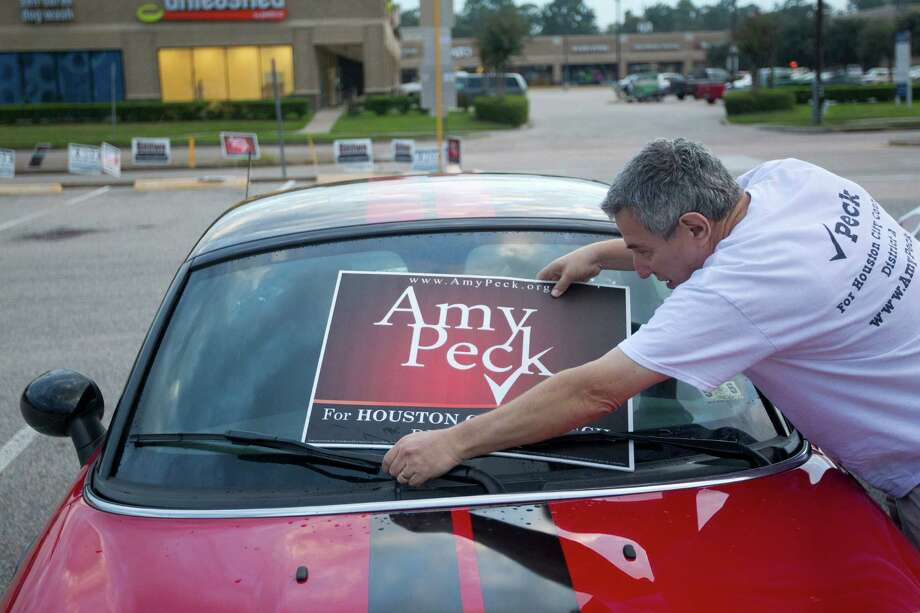 Davis Peck, puts a sign on his car in support of his daughter, Amy Peck, who is running for the Houston City Council District A seat outside an early voting site at the Trini Mendenhall Sosa Community Center Monday, Oct. 21, 2013, in Houston. Photo: Johnny Hanson, Houston Chronicle / Houston Chronicle
