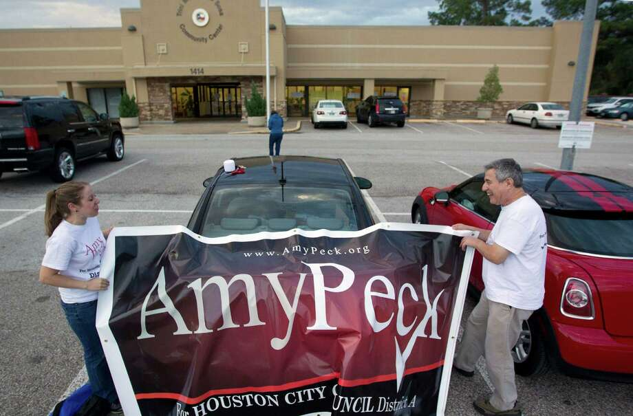 Amy Peck, left, who is running for the Houston City Council District A seat and her father, David Peck, adjust a banner outside an early voting site at the Trini Mendenhall Sosa Community Center Monday, Oct. 21, 2013, in Houston. 