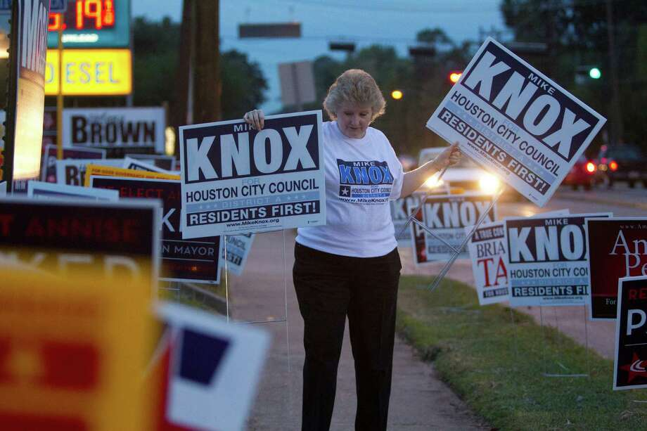 Helen Knox, places signs in support of her husband, Mike Knox, who is running for the Houston City Council District A seat, outside an early voting site at the Trini Mendenhall Sosa Community Center Monday, Oct. 21, 2013, in Houston. Photo: Johnny Hanson, Houston Chronicle / Houston Chronicle