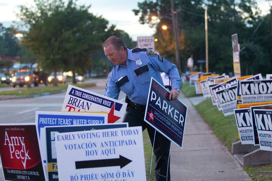 """HPD officer J.J. Mounsey removes candidate bandit signs from the city easement area between the sidewalk and the street outside an early voting site at the Trini Mendenhall Sosa Community Center Monday, Oct. 21, 2013, in Houston.  Officer Mounsey said he had already received complaints about the signs, which are not supposed to be on grassy area on the street side of the sidewalk.  """"People can't see when they try to pull out in their cars,"""" he said. Photo: Johnny Hanson, Houston Chronicle / Houston Chronicle"""
