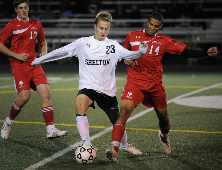 Shelton's Brett Peterson battles for the ball at midfield with Fairfield Prep's Matt Crowe during the first half of their boys soccer matchup at Shelton High School in Shelton, Conn. on Monday, October 21, 2013. Photo: Brian A. Pounds / Connecticut Post