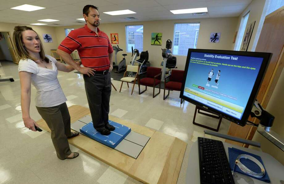 Audrey Paslow works with Brian Van Sise as they use the Balance Testing unit on the machine Oct. 18, 2013 at Ellis Medical in Clifton Park, N.Y.   (Skip Dickstein/Times Union Photo: SKIP DICKSTEIN / 00024266A
