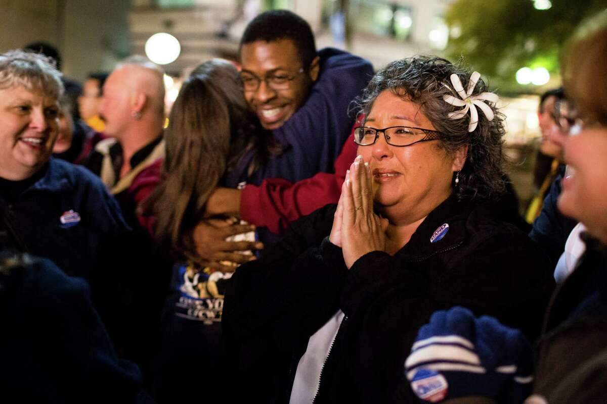 Twenty-seven-year Safeway employee and checker Rhoda Ivie, center right, attempts to hold back tears of happiness during a celebration following the cancellation of a grocery strike by way of a tentative deal to keep grocery workers on the job Monday, Oct. 21, 2013, in Westlake Park in downtown Seattle. Employees will vote on the details in coming days.