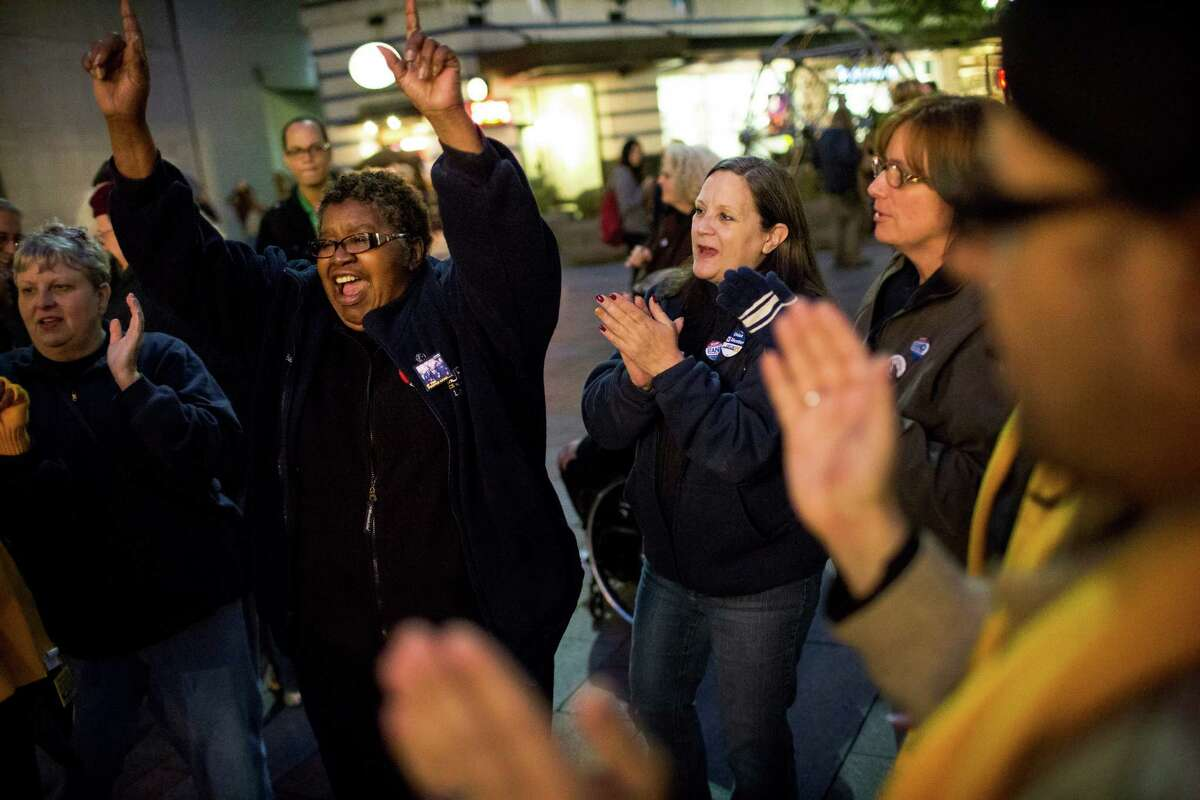 Barbara Rhodes, left, of the United Food and Commercial Workers 21, celebrates the cancellation of a grocery strike by way of a tentative deal to keep grocery workers on the job Monday, Oct. 21, 2013, in Westlake Park in downtown Seattle. Employees will vote on the details in coming days.