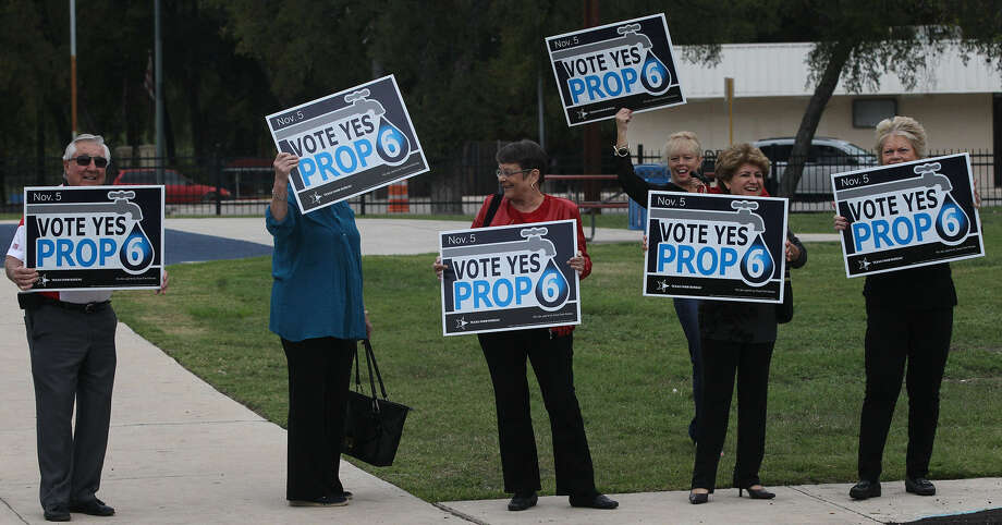 Supporters of Proposition 6 hold signs in the Lion's Field parking lot on Broadway during early voting. Photo: John Davenport, San Antonio Express-News