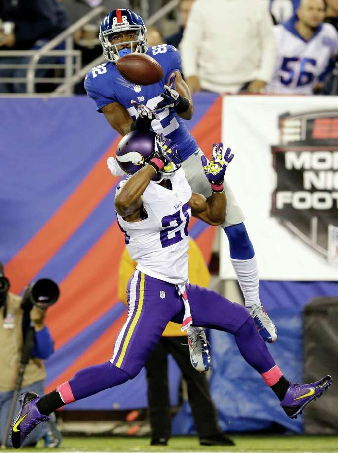 New York Giants wide receiver Rueben Randle (82) catches a pass for a touchdown in front of Minnesota Vikings' Chris Cook (20) during the first half of an NFL football game Monday, Oct. 21, 2013 in East Rutherford, N.J. (AP Photo/Julio Cortez) ORG XMIT: ERU110 Photo: Julio Cortez / AP