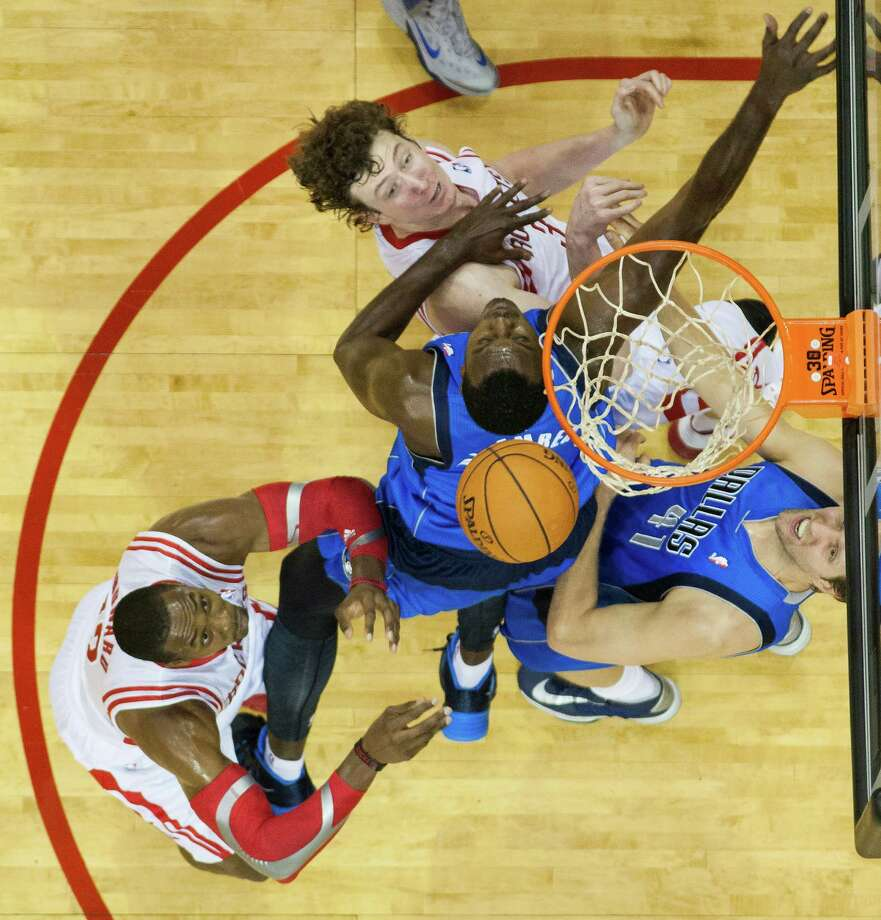 The Rockets' Omer Asik, top, and Dwight Howard, left, fight for a rebound against the Mavericks' Samuel Dalembert (1) and Dirk Nowitzki on Monday night at Toyota Center. Howard ruled the paint, pulling down a game-high 17 rebounds. Photo: Smiley N. Pool, Staff / © 2013  Houston Chronicle