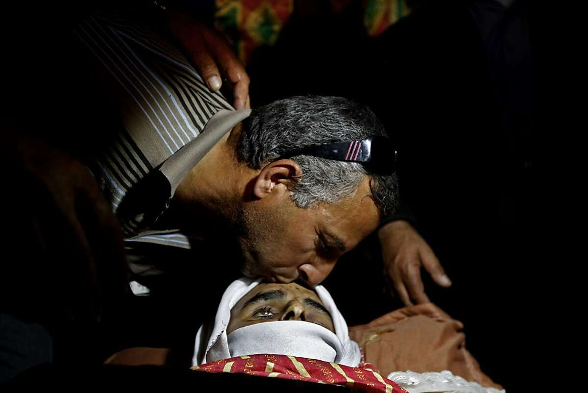 A Palestinian man kisses the forehead of Younis Radaideh, 28, during his funeral in the Al Ubiedyeh village near the West Bank city of Bethlehem, Monday, Oct. 21, 2013. Radaideh was killed last Thursday by Israeli forces after he drove a tractor into an army base north of Jerusalem. (AP Photo/Majdi Mohammed)