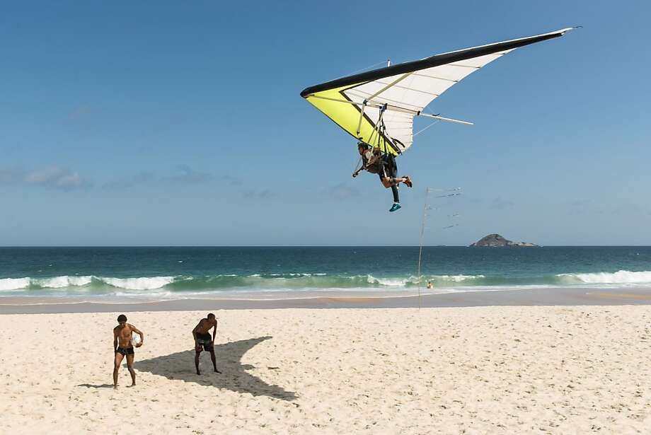 Hold it right there, OK? ... I'm enjoying this shade: A hang glider floats over Sao Conrad beach in Rio de Janeiro. Photo: Yasuyoshi Chiba, AFP/Getty Images
