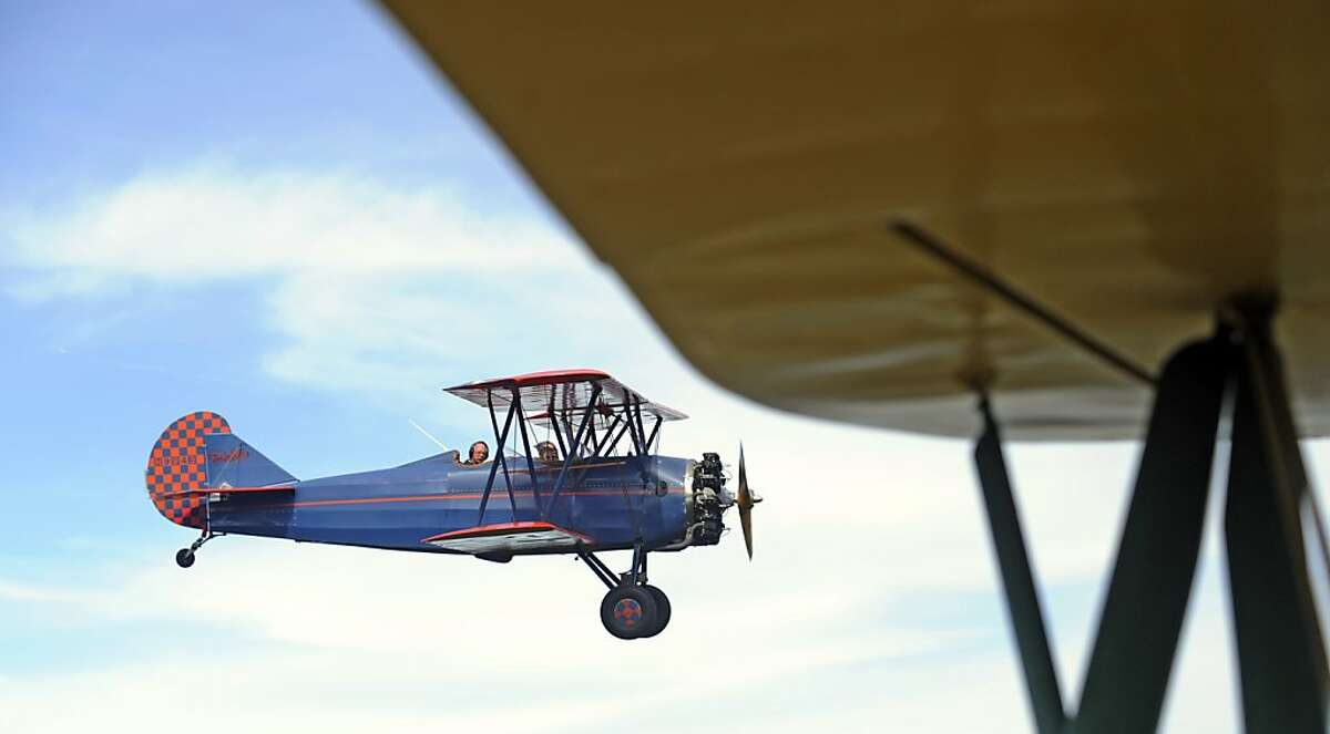 A 1929 Curtiss- Wright Travel Air Biplane piloted by David Mars carrying Donny Harrison and Penny McClain files over Gadsden while giving rides from Northeast Alabama Airport in Gadsden, Ala., on Monday, Oct. 21, 2013. (AP Photo/The Gadsden Times, Eric T. Wright)