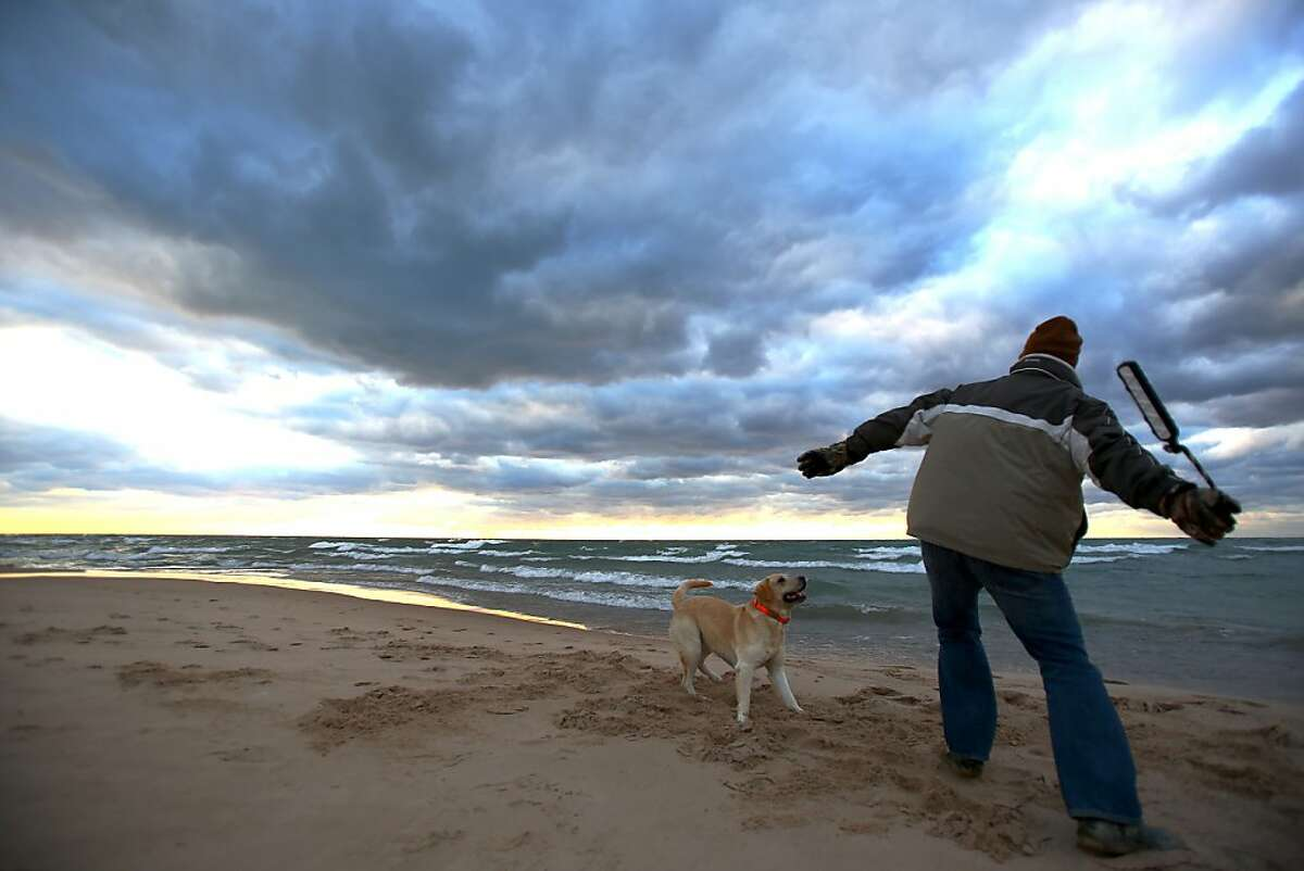 Matt Nordberg and his pup Cal play a game of fetch on a cold fall day at Silver Beach in St. Joseph, Mich. Monday Oct 21, 2013. Monday night's forecast calls for the first freezing temperatures of the season in Southwest Michigan but that won't stop Cal from jumping in the water;