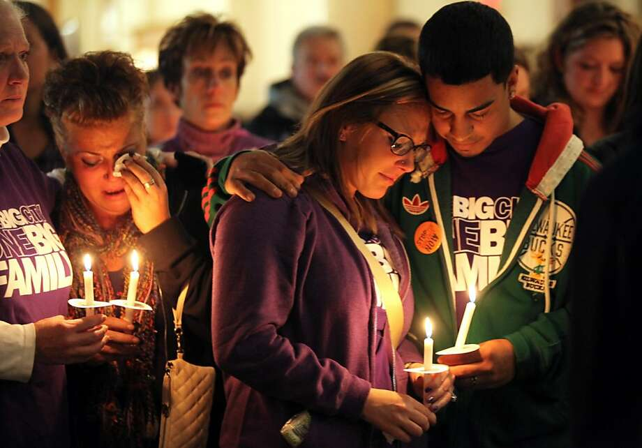 A group of people, who wished to remain unidentified, hold candles during a vigil marking the one-year anniversary of the Azana Salon & Spa shooting, Monday, Oct. 21, 2013 in the Milwaukee City Hall rotunda. Radcliffe Haughton shot and killed his estranged wife, Zina, and two others at the Brookfield spa on Oct. 21, 2012, before fatally shooting himself. Four others were wounded. (AP Photo/Milwaukee Journal-Sentinel, Mike De Sisti) Photo: Mike De Sisti, Associated Press