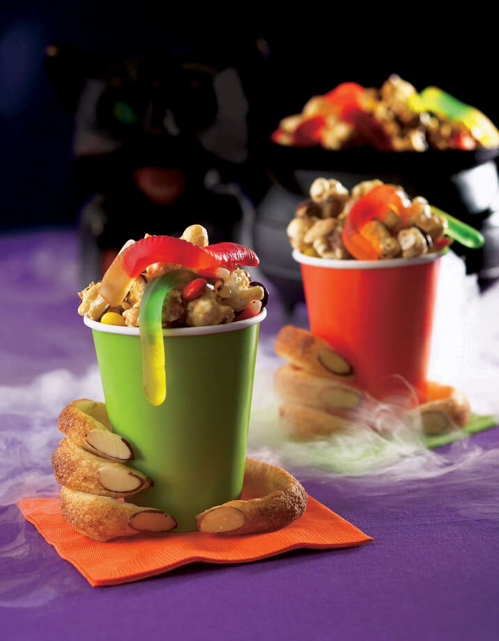 ** FOR USE WITH AP WEEKLY FEATURES **  This photo provided by Woman's Day shows Monster Munch mix piled into colored cups grasped by Witchy Fingers _ sweetly scary treats for Halloween, easily made at home. Recipes and photo are from the October issue of Woman's Day magazine. (AP Photo/Woman's Day/John Uher) Photo: JOHN UHER, HO / WOMAN'S DAY