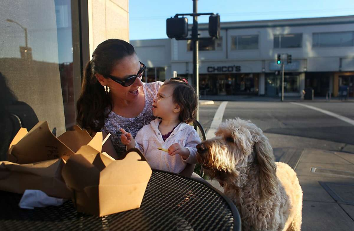 Michele Fishbein reacts to her daughter, Julia Fishbein Perlman, as they share a meal outside of A.G. Ferrari Foods on October 19, 2013 across from the Laurel Village Shopping Center in San Francisco, Calif. At right is the family's dog, Denver.