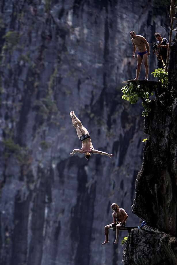 In this handout image provided by Red Bull, Michal Navratil (top) of the Czech Republic and Sports Director, Hassan Mouti (bottom) of France watch on as Alain Kohl (C) of Luxembourg dives from the 27 metre platform at Maya Bay in the Andaman Sea during the final stop of the 2013 Red Bull Cliff Diving World Series on October 21, 2013 at Phi Phi Island, Thailand. Photo: Handout, Red Bull Via Getty Images