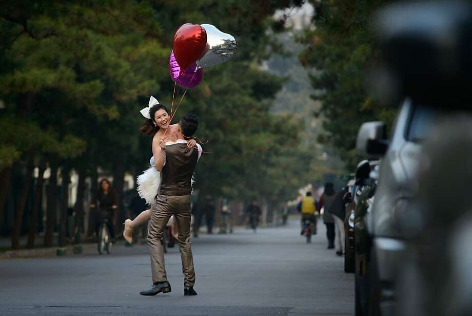 Oof, you're still pretty heavy despite the balloons: A bride is swept off her feet by her man on a street in Beijing. Photo: Ed Jones, AFP/Getty Images