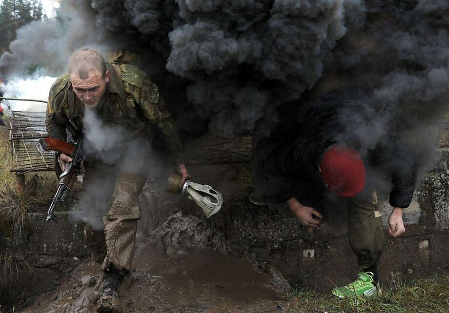 "Trial by fire and mud: Would-be Interior Ministry commandos run through a smoky obstacle course during ""Madder Beret"" final exams outside Minsk. Soldiers who pass the tests receive a burgundy-colored beret signifying they have qualified as members of the Belarus Interior Ministry elite Special Forces. Photo: Viktor Drachev, AFP/Getty Images"